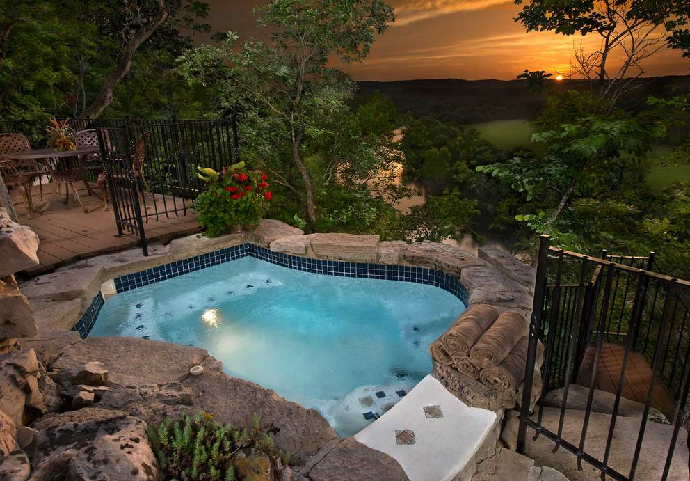 Outdoor patio with seating area and hot tub overlooking the Lake Taneycomo at sunset.